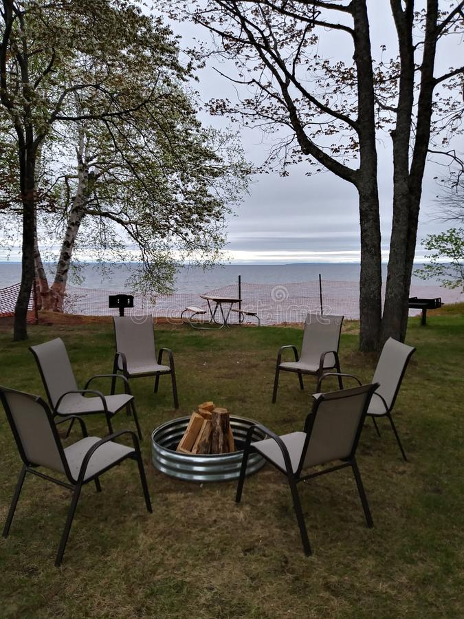 Picnic firewood relax chairs fire pit Sandy beach Lake water horizon Birch tree trunk branches white royalty free stock photography