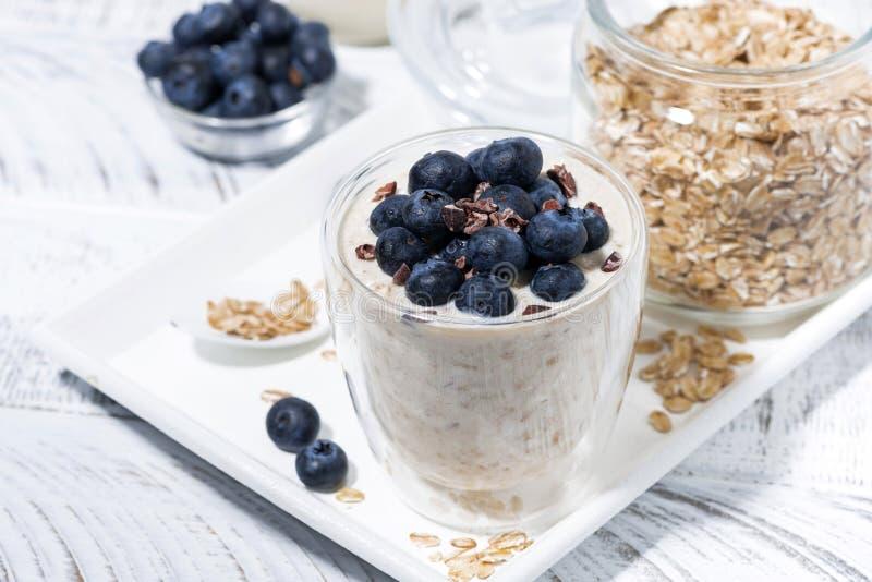 Bircher muesli with fresh blueberries on white table stock image