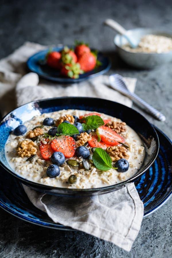Bircher-muesli mit Erdbeeren, Blaubeeren, chia Samen, Walnüssen, Sonnenblumensamen und Kürbiskernen lizenzfreies stockfoto