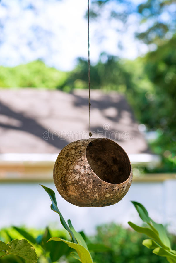 Bird animal feeder nest outdoors hanging on a string from the roof.  royalty free stock photo