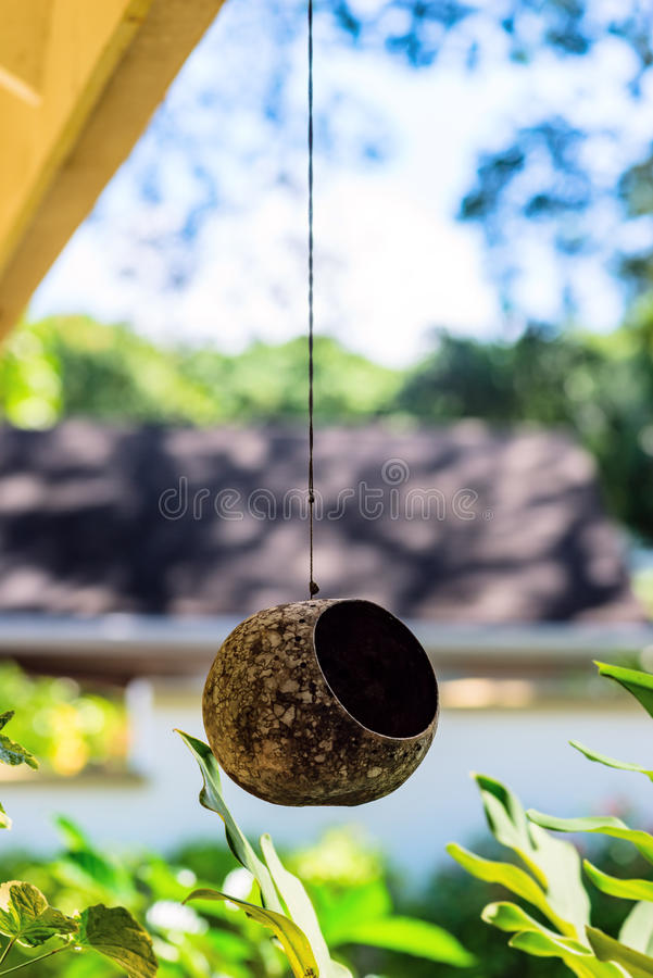 Bird animal feeder nest outdoors hanging on a string from the roof. Creative handmade recycled royalty free stock photo