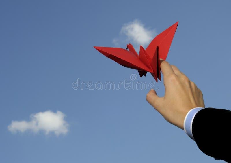 Origami bird in hand against sky royalty free stock photos