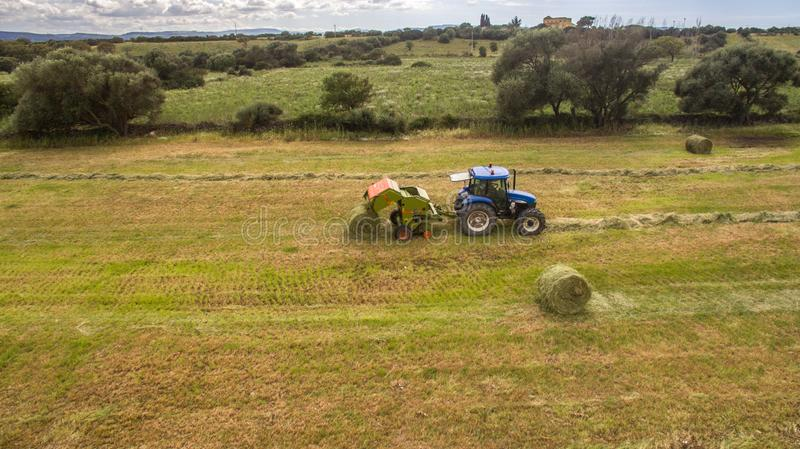 Bird eye of Man at work on the tractor with hay baler stock photos
