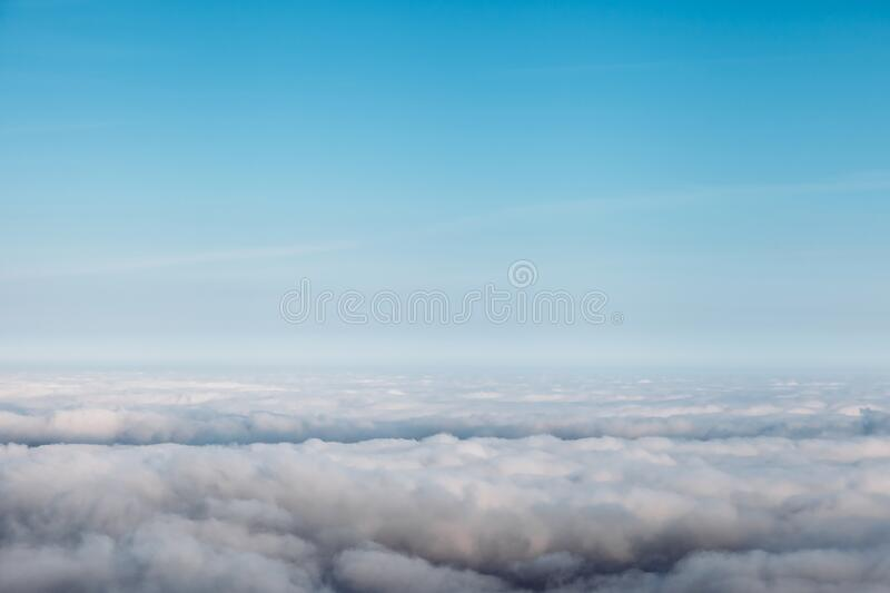 Bird eye view at clouds in blue sky top view from drone from airplane window stock photo