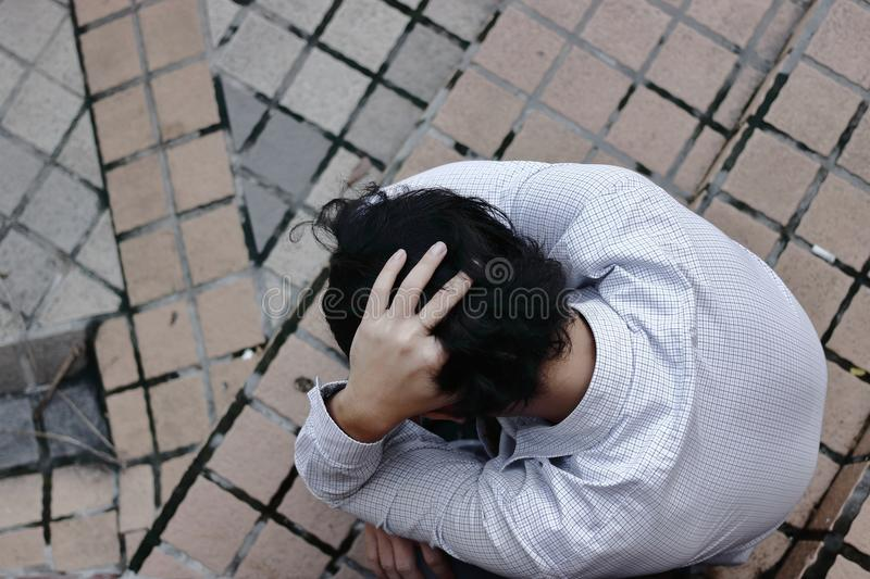 Bird eye view of depressed stressed Asian business man suffering from trouble. stock photo