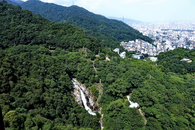 Bird eye view of water fall in forest hill of Nunobiki National. Park and town cityspace of Kobe , Japan royalty free stock photos