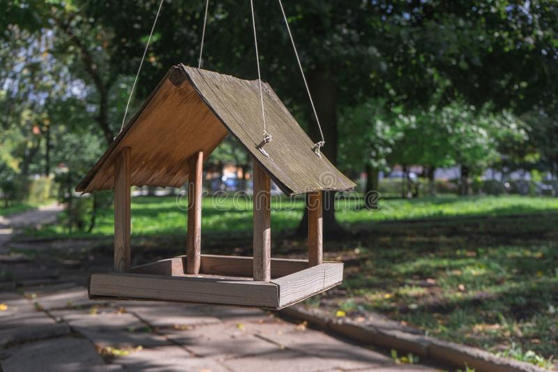 Bird feeder in the form of a house hanging on a tree in Park stock photos