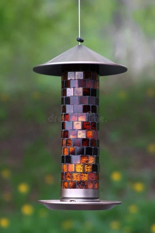 Bird feeder. Multi colored glass bird feeder in the backyard royalty free stock photography