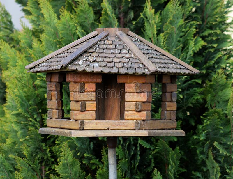 Bird feeder. Nice and small handcrafted wooden bird feeder with wicker roof royalty free stock photo