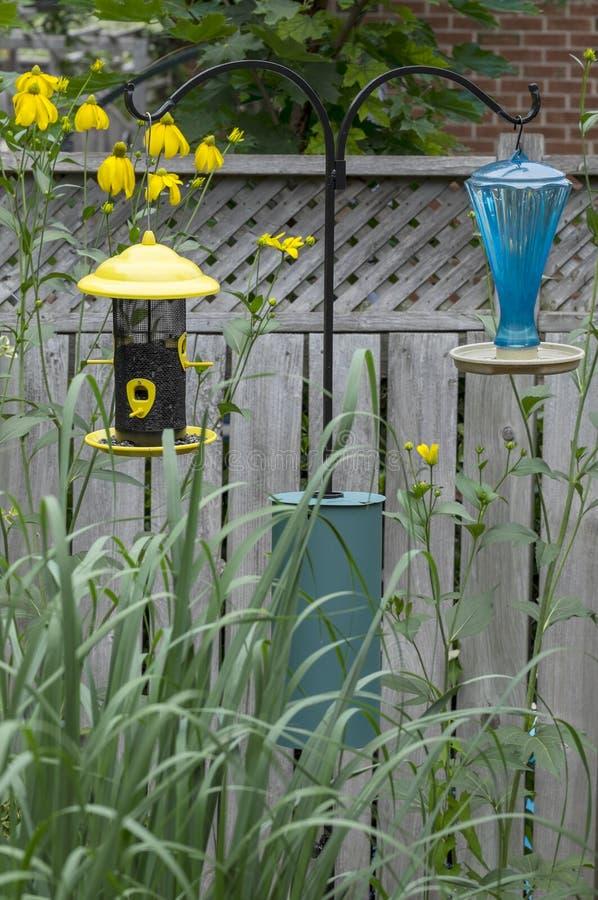 Bird Feeder #1. Bird feeder, water bottle and a squirrel baffle in a garden royalty free stock photos