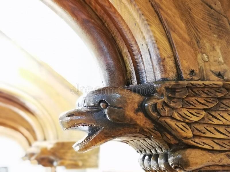 Bird head carved in wood. Details wooden interior sculpture at the corner of the arcade royalty free stock photography