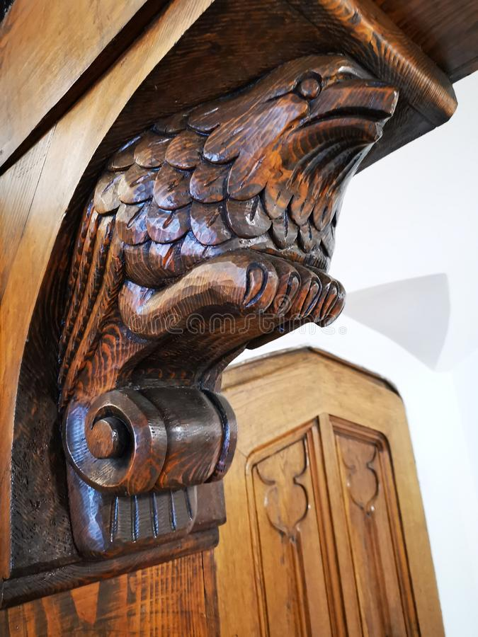 Bird head carved in wood. Details wooden interior sculpture at the corner of the arcade royalty free stock photo