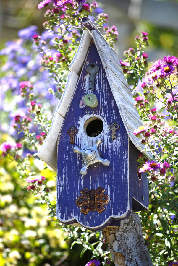 Bird House. Old purple wooden bird house in garden royalty free stock images