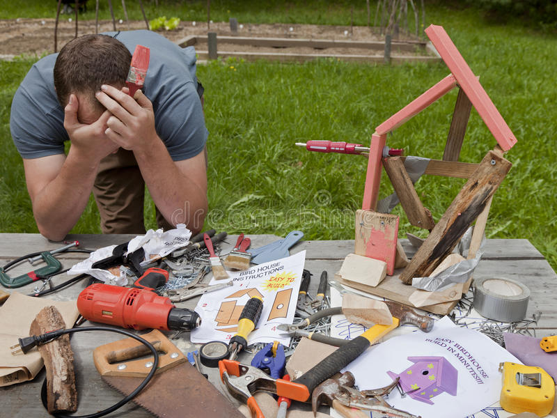 Bird House Fail. A man is frustrated and angry at building a bad birdhouse royalty free stock photography