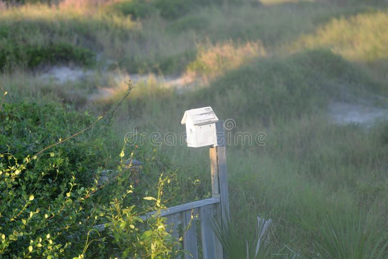 The bird house sits on the edge of a large sand dune and two hundred yards from the ocean waves royalty free stock photography