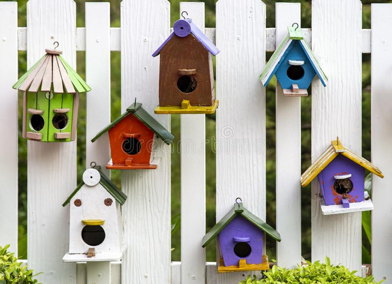 Bird house on wood fence. In the garden stock image