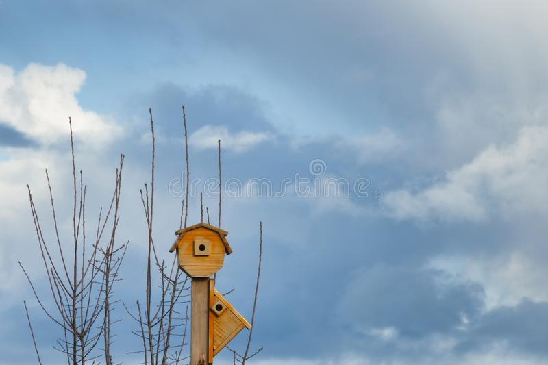 Bird Houses and Cloudy Skies. Copyspace available in this scene with two bird houses on a post under cloudy skies royalty free stock image