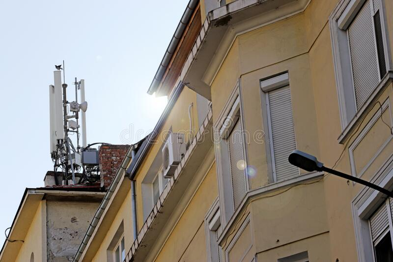 Bird landed on a High Tech Telecommunication Antenna Tower mounted on a building.  stock images