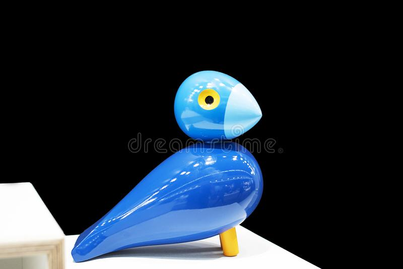 Bird made of wood, carved figure close-up. Black background with blue shiny bird made of wood royalty free stock photography