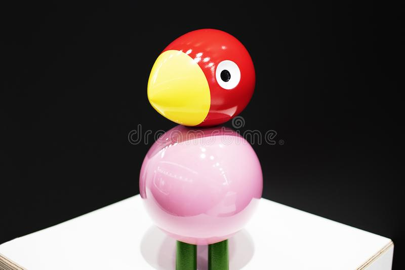 Bird made of wood, carved figure close-up. Black background with pink bird and red wood head. White round eye stock photo