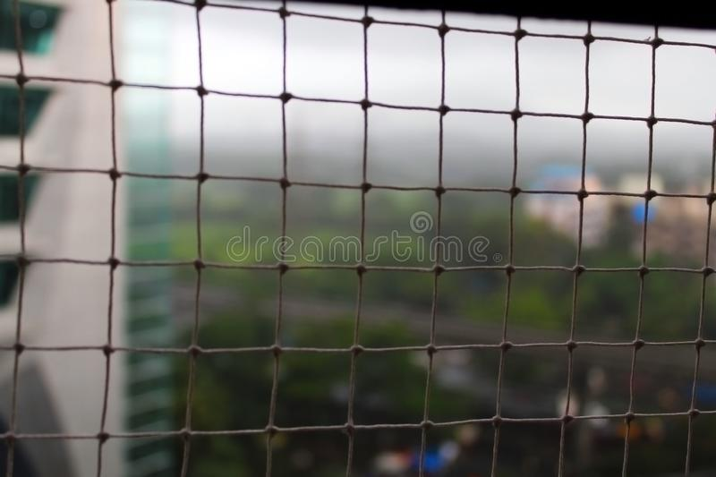Bird net outside the sliding window with an out-of-focus view of the highway, office buildings and green patches of land stock images