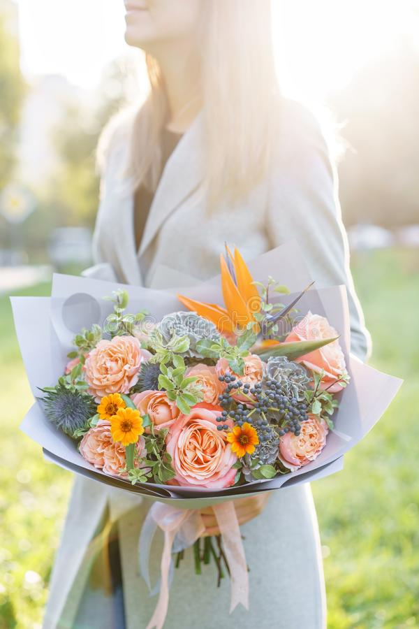 Bird of paradise flower, beautiful spring bouquet. Young girl holding a flower arrangement with variety of colors. Violet, blue and peach color flower stock photo