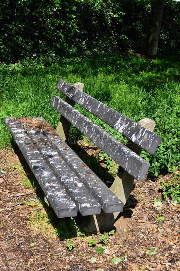 Bird poo droppings. Nuisance: bird poo droppings at bench in park stock photo