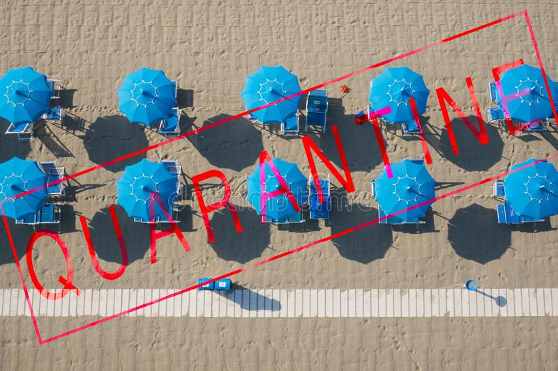 Bird`s eye view of a beach aligned with umbrellas, overimpressed the text quarantine, due to  covid pandemia the touristic season stock photos
