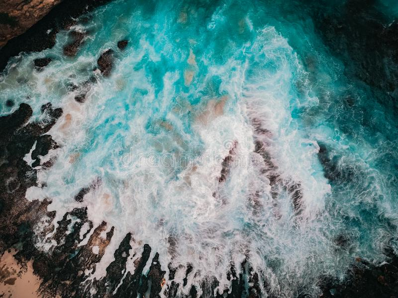 Bird`s eye view of the broken beach in Nusa Penida, Indonesia. Waves and foam, abstract background, drone photography. Bird`s eye view of the broken beach in royalty free stock photos