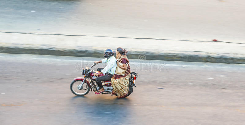 Bird's eye view onto a couple on a motorbike in Jaipur. JAIPUR, INDIA - NOV 13, 2011: couple riding on a bike (blurred motion). Motorbike is the most favorite stock images
