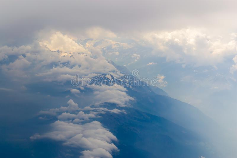 The bird's eye view on the sky with the huge fluffy dramatic clouds above the Alps stock photo