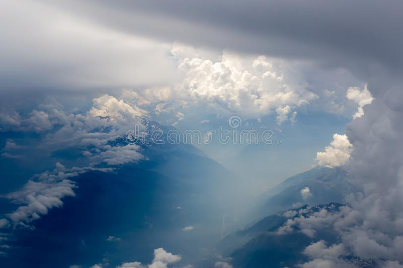 The bird's eye view on the sky with the huge fluffy dramatic clouds above the Alps royalty free stock photos