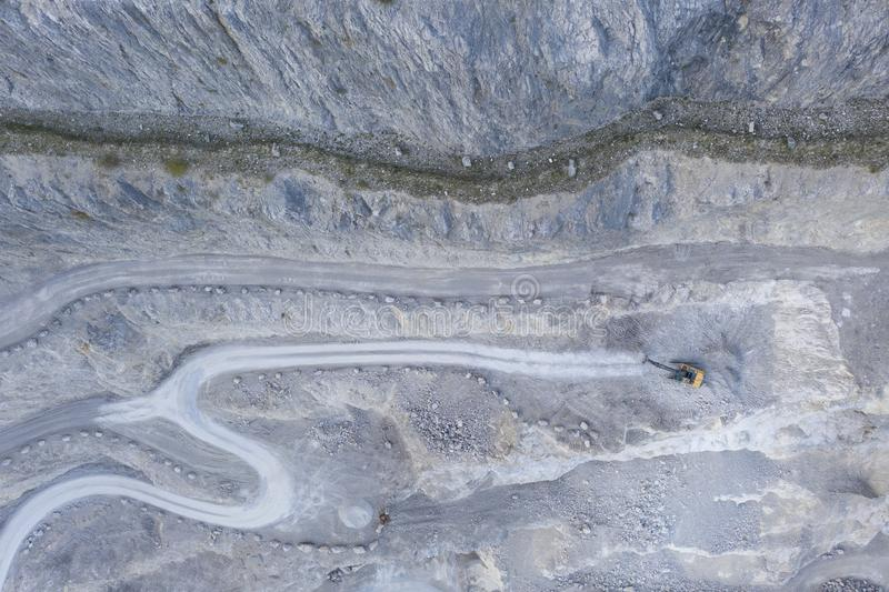Bird`s eye view to stone pit quarry with shovel excavator. Tracks and roads royalty free stock photography
