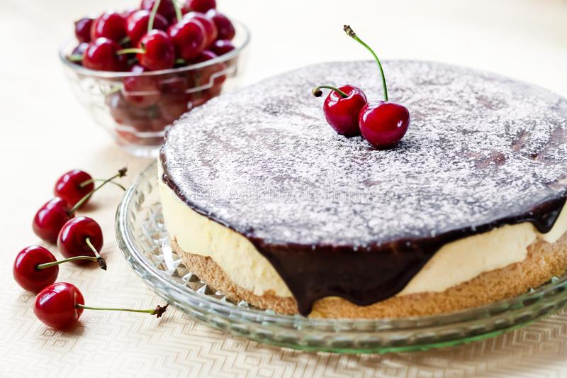 Bird`s Milk souffle cake, covered with chocolate glaze and decorated with ripe cherries stock photos