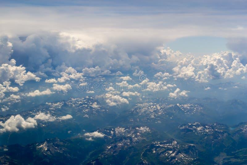 Bird' s oogmening over de hemel met de reusachtige pluizige dramatische wolken boven de Alpen royalty-vrije stock foto's