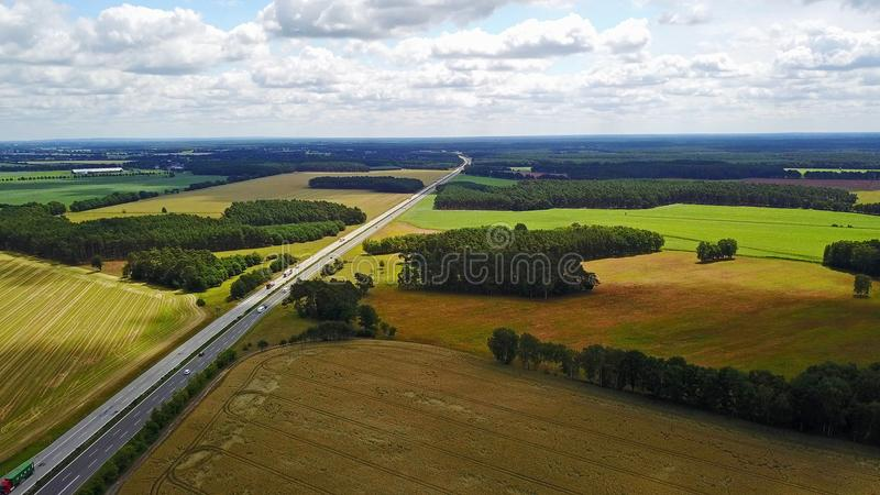 Bird View Highway in Germany. Bird view of one highway extends to remote and across green and yellow fields and dark green forests in Germany in summer sunny day royalty free stock images