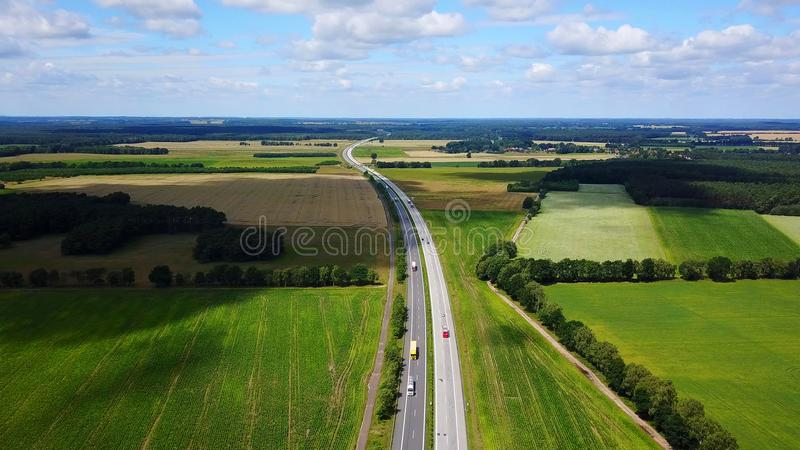 Bird View Highway in Germany. Bird view of one highway extends to remote and across green and yellow fields and dark green forests in Germany in summer sunny day stock photography