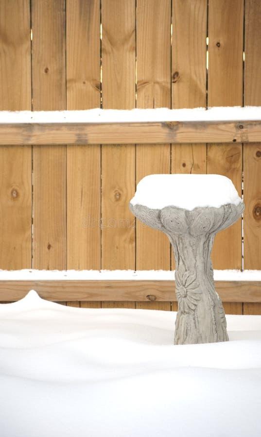 Birdbath nevado delante de la cerca imagen de archivo libre de regalías