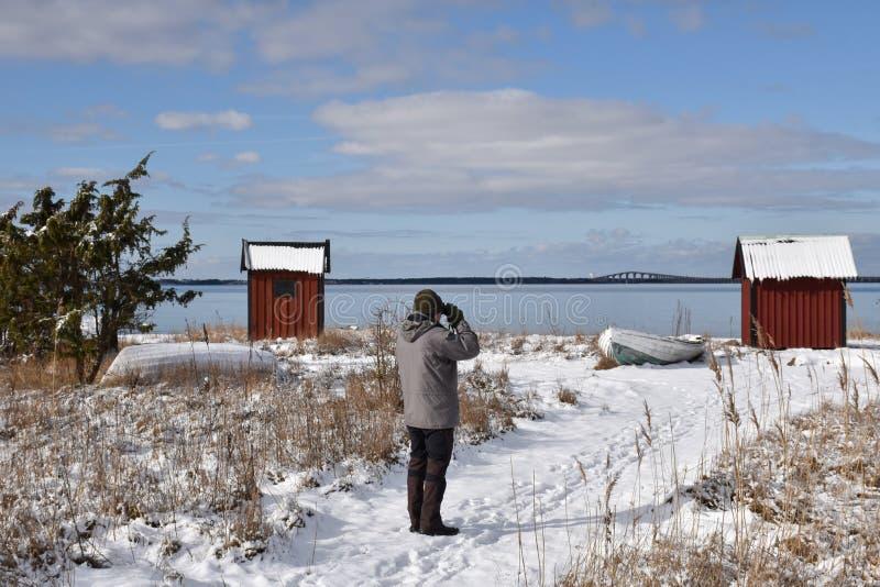 Birder que mira por la costa en la estación del invierno fotos de archivo