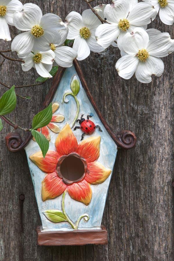 Birdhouse auf altem hölzernem Zaun mit Hartriegeln stockfotografie