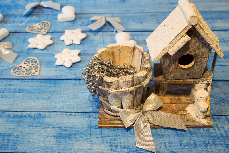 Birdhouse and Christmas decoration on blue background stock photography