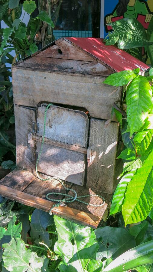 A birdhouse made of wooden boards with a wooden door and a red roof. Shelter for gray Eastern Screech Owl on Bali island in. Indonesia. Old wooden birdhouse stock photography