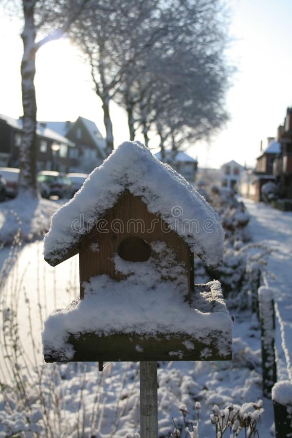 Birdhouse. A birdhouse near a small stream of water in winter royalty free stock photography