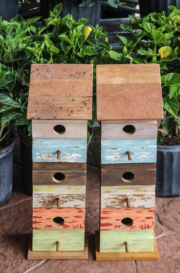 2 birdhouses мульти-рассказа выглядящих домодельн для продажи около в горшке заводов гибискуса в весеннем времени стоковая фотография rf