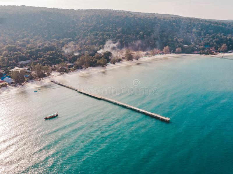 Birds eye drone aerial view of single pier in crystal clear blue sea on secluded beach on Cambodian island Koh Rong on sunny stock photos