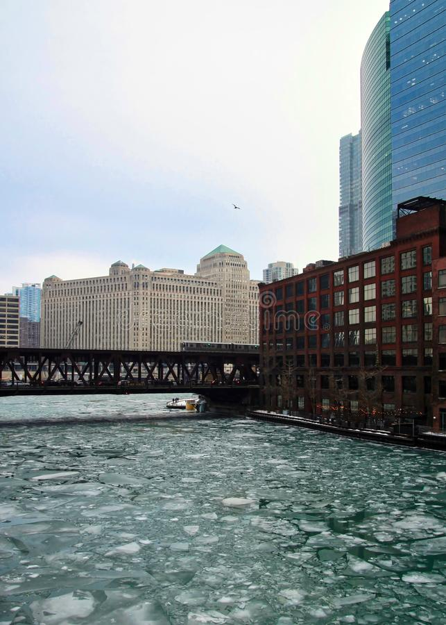 Birds fly over an ice chunk covered, frozen Chicago River, aqua blue and running through Chicago Loop while el train speeds by. stock image