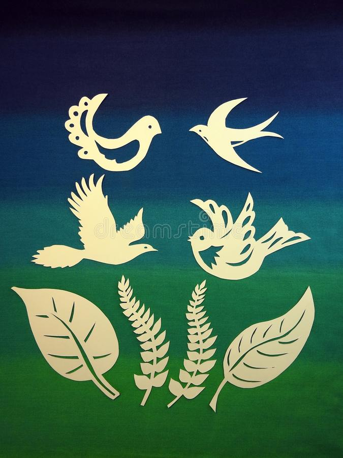 Birds and leaf cut from paper. Beautiful birds and leaves cut from white paper on colorful background royalty free stock photo