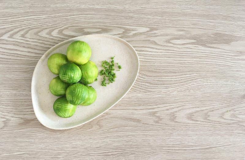 Birdseye-Ansicht von grünen Zested-echten Limetten auf freundlicher Platte Eco stockbilder