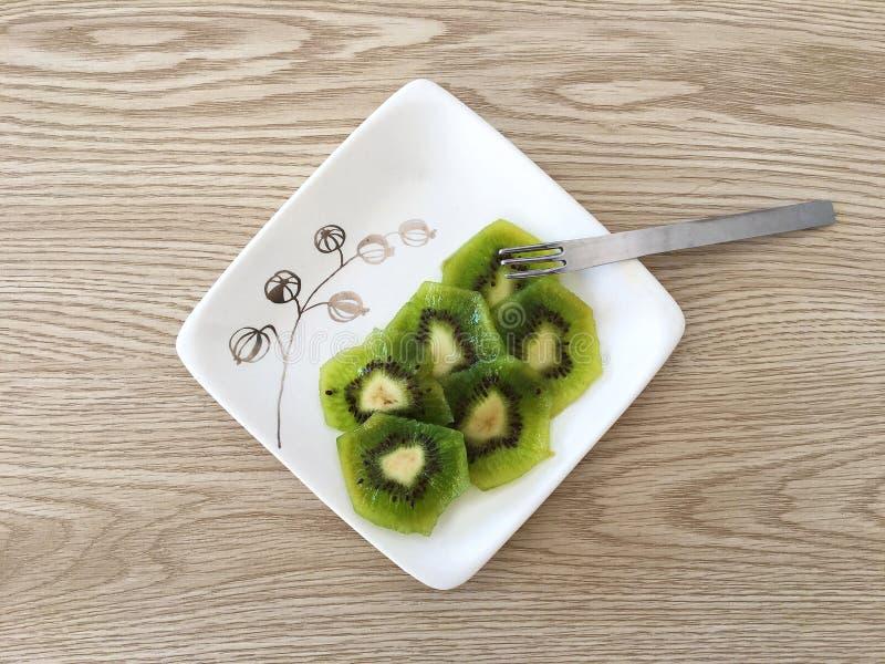 Ripe Sliced Kiwi on Modern White Plate with Light Oak Wood Background royalty free stock photo