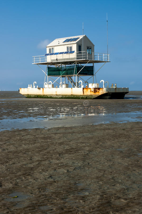 Birdwatch cabin, Wadden Sea. Birdwatch cabin on the tidal flats at low tide of the wetlands, Wadden Sea, Netherlands stock image